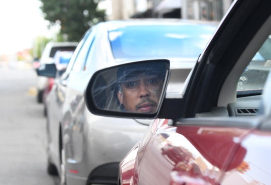 Marcus Thatcher seen in the side mirror of his vehicle near the intersection of Holbrook Ave. and Joseph Campau Street, where he was was held at gunpoint and put in handcuffs by Hamtramck police because he was told he fit the description of an armed robber in the area, in Hamtramck on July 13, 2020.