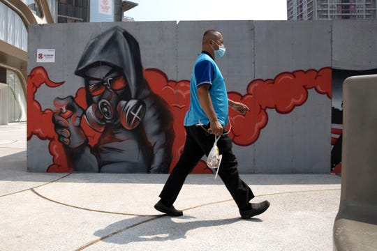 A delivery man wearing a mask to curb the spread of the coronavirus walks past graffiti artwork in Beijing Monday, July 13, 2020. China reported eight new cases, all of them brought from outside the country, as domestic community infections fall to near zero.