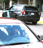 A Hamtramck Police vehicle passes by Marcus Thatcher in his vehicle near the intersection of Holbrook Street. and Joseph Campau Ave, where he was was held at gunpoint and put in handcuffs by Hamtramck police because he was told he fit the description of an armed robber in the area, in Hamtramck on July 13, 2020.