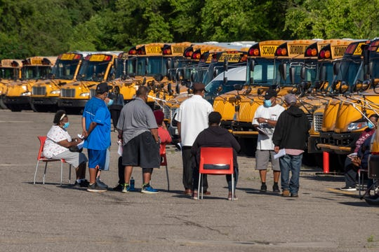 Workers sit among idle school buses after demonstrators blocked the driveways of the Detroit Public Schools West Side Bus Terminal to keep the buses from running on the first day of summer school, in Detroit, July 13, 2020. A lawsuit seeks to end summer school.