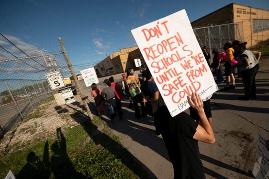 Demonstrators block the driveways of the Detroit Public Schools West Side Bus Terminal to keep school buses from running on the first day of summer school, in Detroit, July 13, 2020. Concerns about COVID-19 and a lack of safety measures prompted the protesters to demand that schools close.