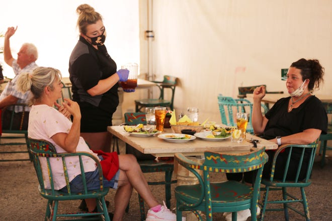 Double Eagle waitress Nicole James serves patrons Kirstie Robles and Andrea Schneider on the restaurant's patio, Monday July 13. 2020.