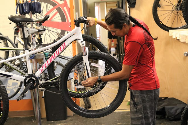 Bisti Bicycles bike technician Shane Rakestraw checks the front tire of a bike on Monday, July 13, 2020, in Farmington.