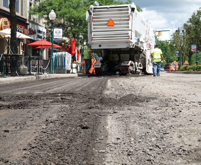 Equipment works on striping a layer of the road surface along Main Street in downtown Plymouth on July 13, 2020.