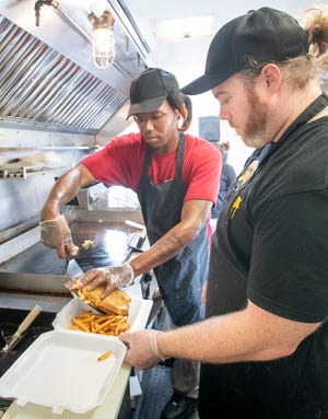 Cook Demitrius Arnold, left, and owner Kendrick Hobbs plate a mac and cheese burger melt July 13 at the new Melt food truck in Pensacola.