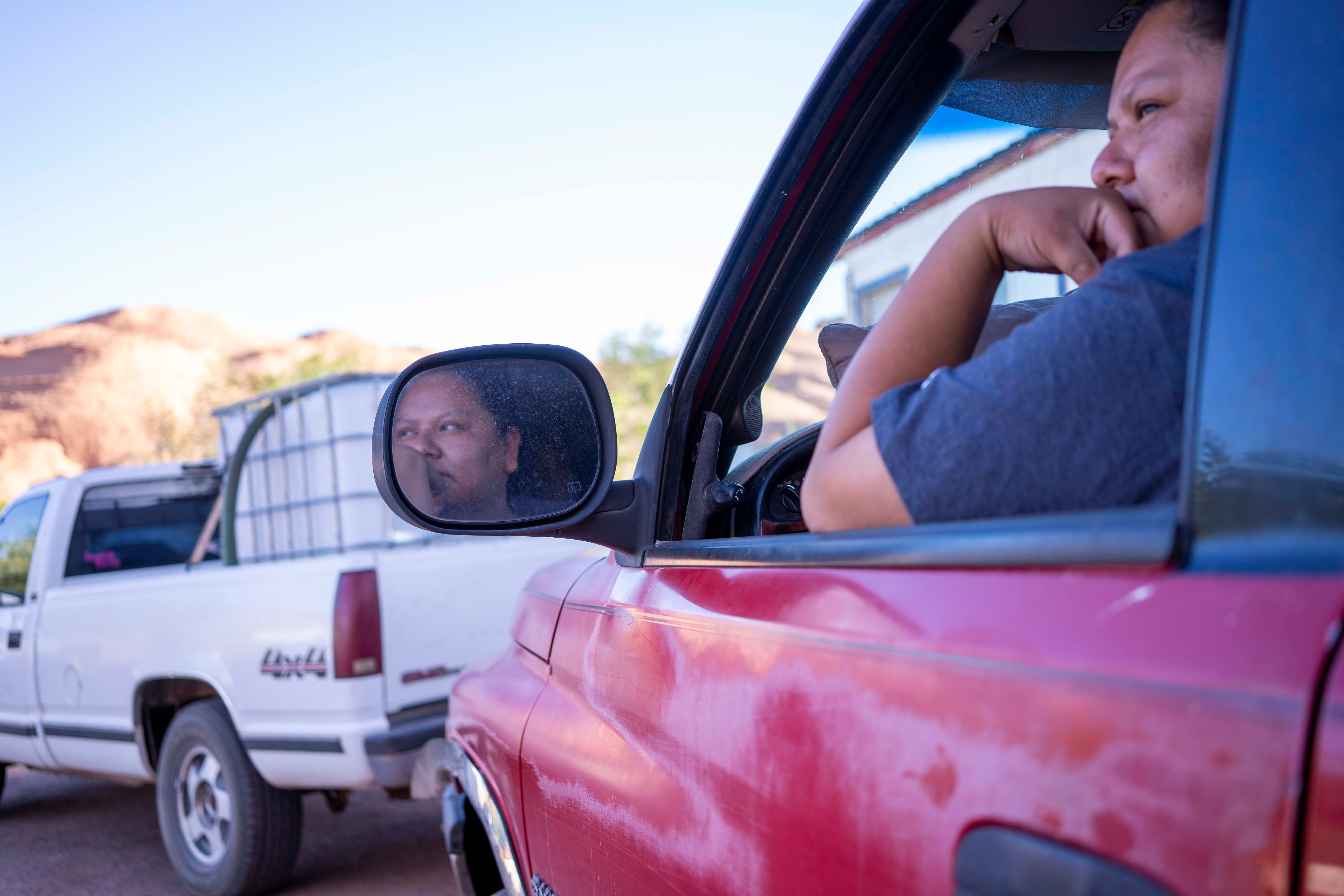 Heidi Nelson waits in line at the water spigot in the community of Goulding, Utah, on the Navajo Nation. She said one tankful of water would be enough to last her family two or three days.