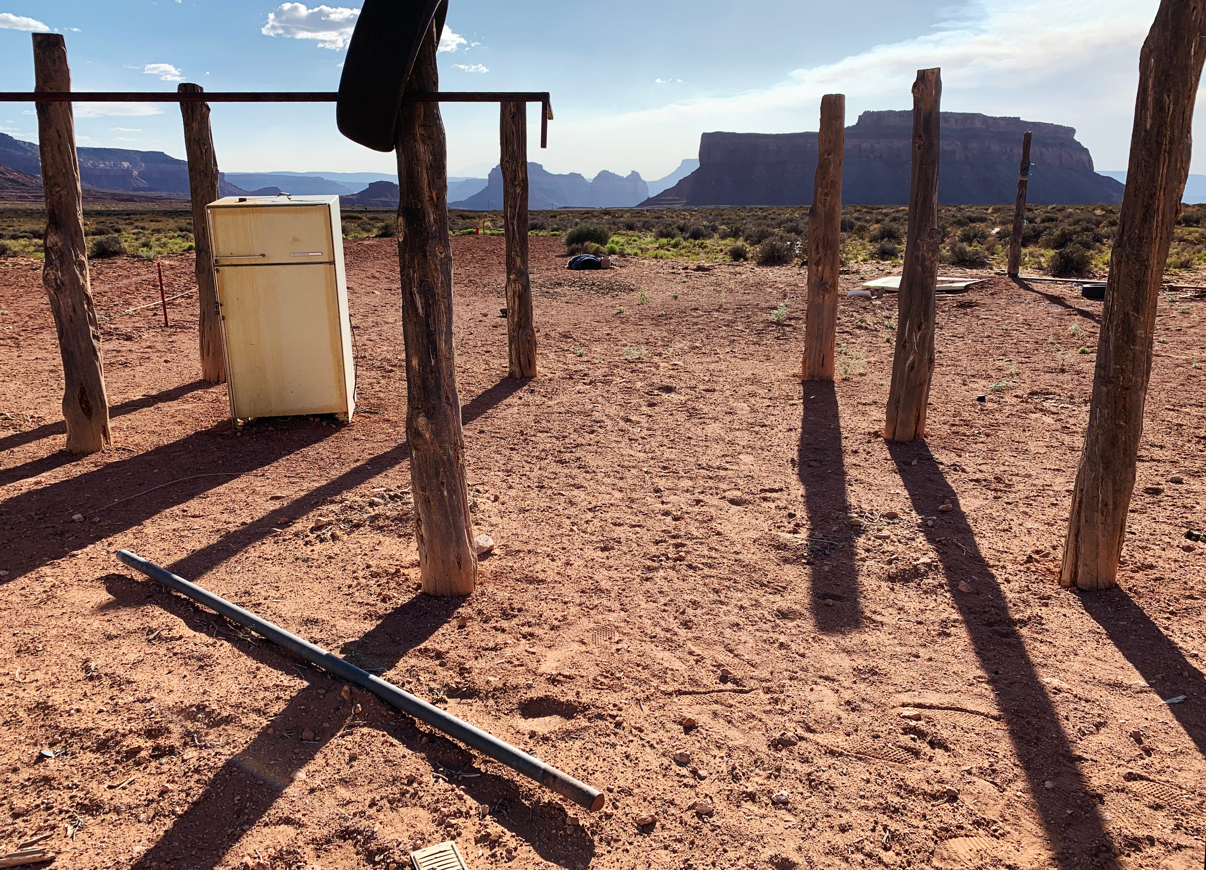 Wood posts cast shadows in Monument Valley on the Navajo Nation, where many people live in homes without running water or electricity.