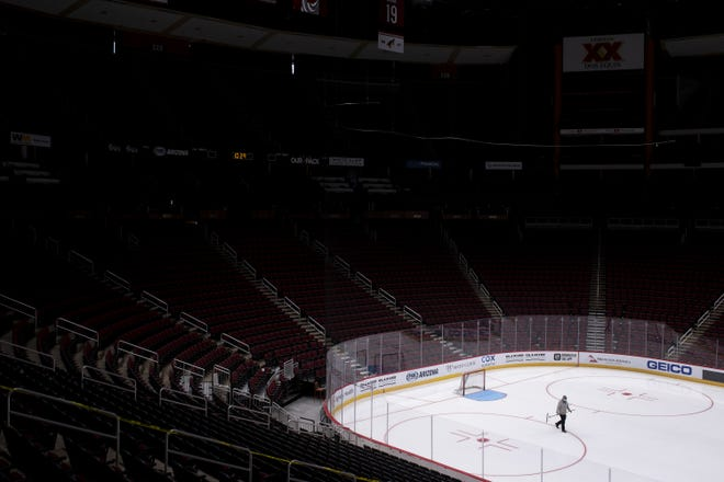 An Arizona Coyotes employee prepares the ice during the first day of training camp on July 13, 2020, at Gila River Arena in Glendale, Ariz. NHL owners and players approved an agreement Friday to resume the season.