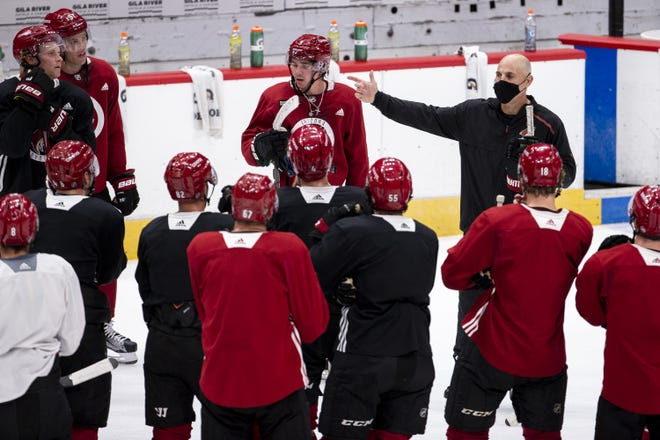 Arizona Coyotes head coach Rick Tocchet talks to players after practice during the first day of training camp on July 13, 2020, at Gila River Arena in Glendale, Ariz. NHL owners and players approved an agreement Friday to resume the season.