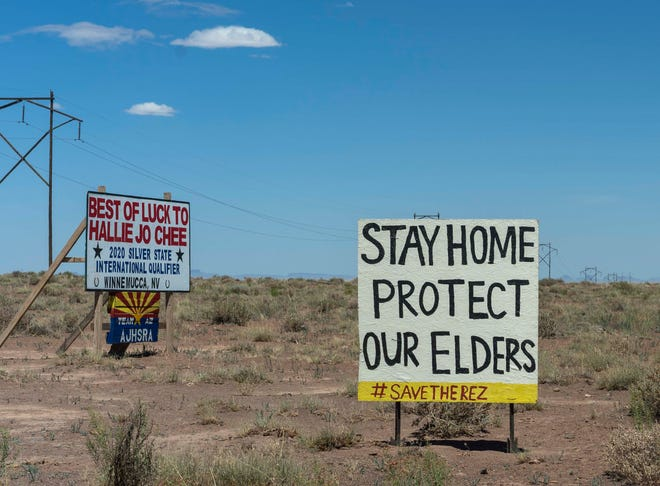 A sign next to a water-collection point in Leupp, Arizona, urges people to stay home to curb the spread of COVID-19. As older residents on the Navajo Nation have tried to stay isolated at home, relatives and community members have stepped in to haul water for them.
