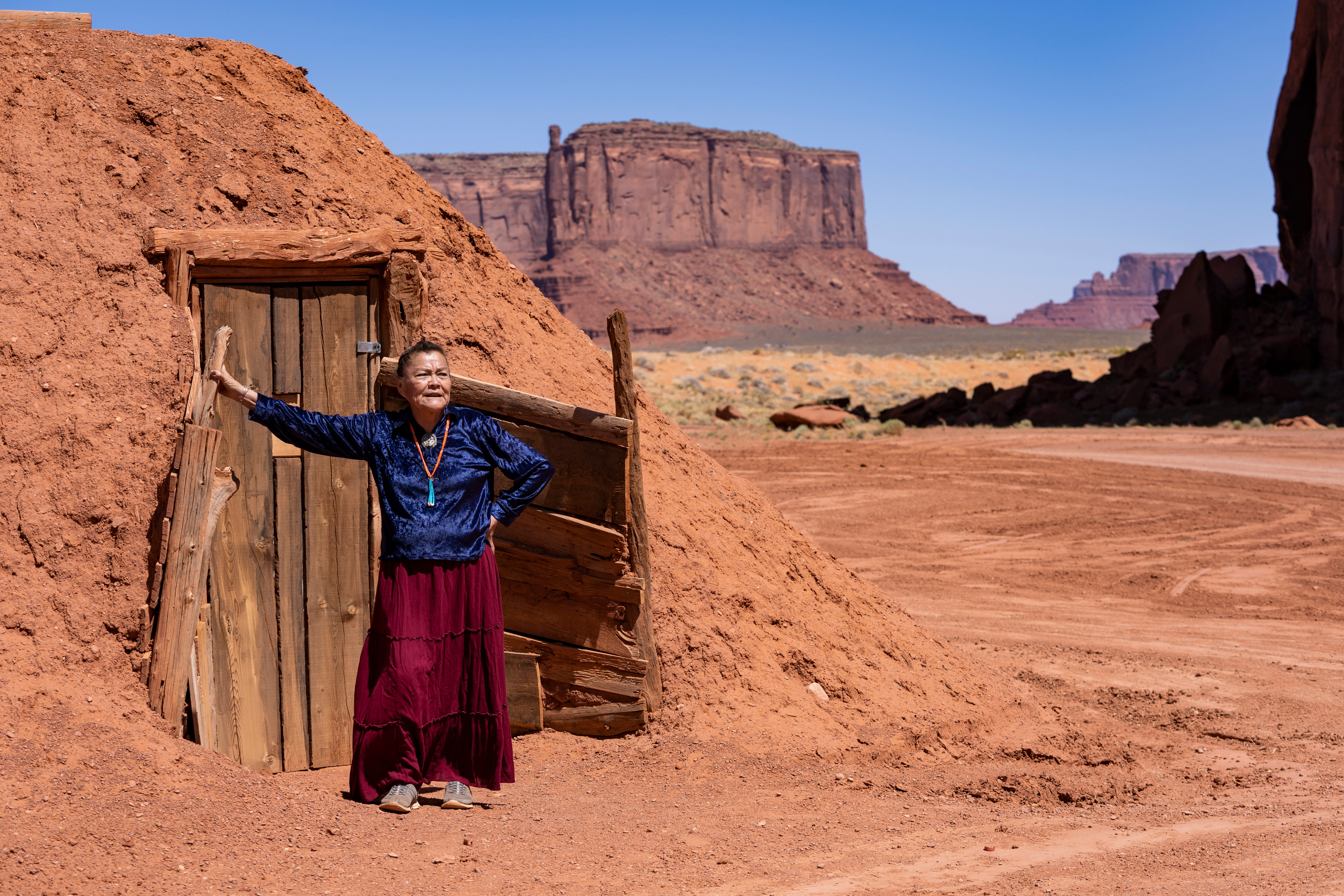 Effie Yazzie stands by a traditional hogan next to the house where she lives in Monument Valley on the Navajo Nation. She recently fell sick with COVID-19 but has since bounced back.