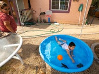 Noel Zepeda, 3, stays cool in a kiddie pool, as his grandmother, Guadalupe Zepeda, looks on at her home in Phoenix on July 13, 2020. Temperatures at Phoenix Sky Harbor International Airport hit 114 degrees, tying a record high for the date, according to the National Weather Service.