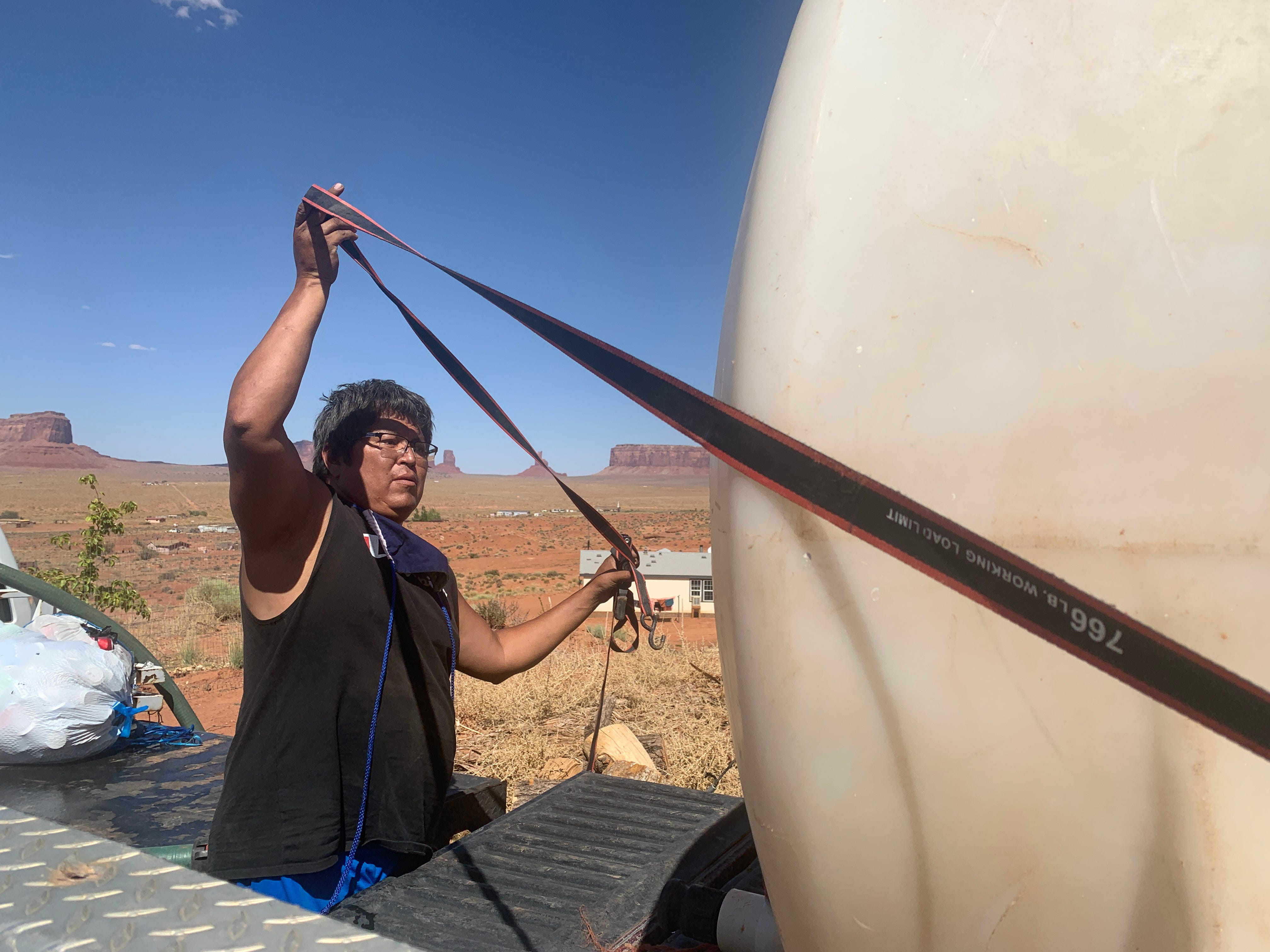 Tommy Rock moves a water barrel onto the back of his truck, preparing to get water in Monument Valley, Utah, on the Navajo Nation.