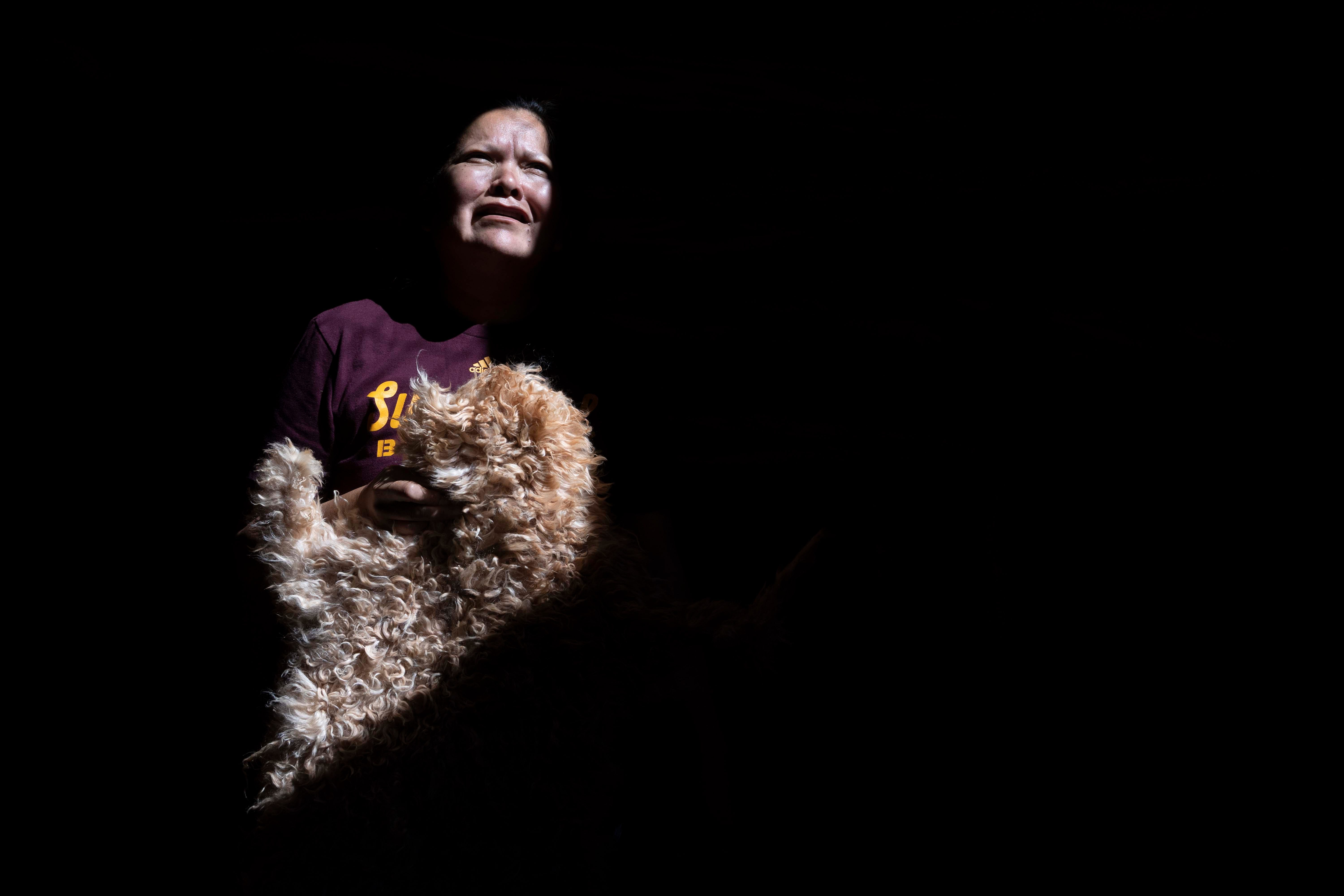 Elvina Holiday, 40, holds a sheepskin beside her family's home in Monument Valley on the Navajo Nation. Her family's primary business was tourism, including leading visitors on horse tours. With the coronavirus keeping visitors away, their business is at a standstill.