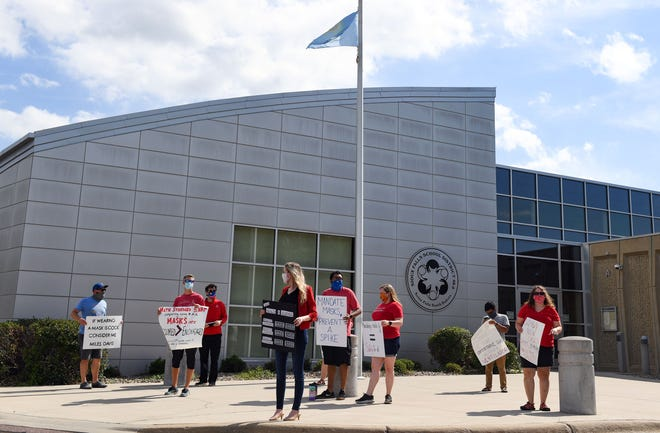 School district employees, including teachers, instruction coaches and custodians, protest in-person learning without a mask mandate on Monday, July 13, at the Sioux Falls School District Instructional Planning Center.