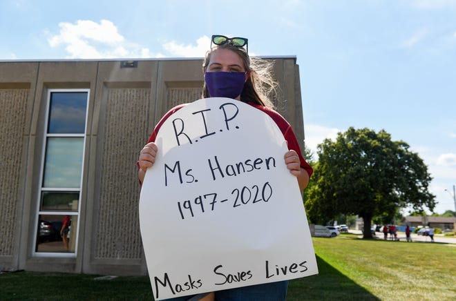 "Lizzie Hansen, A+ teacher, holds a sign representing her own gravestone while protesting the school board's return to learning plan on Monday, July 13, outside the Sioux Falls School District Instructional Planning Center. ""This is a real possibility,"" she said. Hansen has a compromised immune system and says that in-person learning without a mask mandate is irresponsible. ""My students deserve to be successful and deserve to be safe."""
