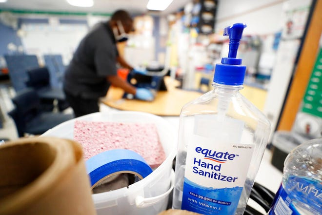 A bottle of hand sanitizer sits on a cart as Des Moines Public Schools custodian Tracy Harris cleans a chair in a classroom at Brubaker Elementary School, Wednesday, July 8, 2020, in Des Moines, Iowa. As the Trump administration pushes full steam ahead to force schools to resume in-person education, public health experts warn that a one-size-fits-all reopening could drive infection and death rates even higher. (AP Photo/Charlie Neibergall)