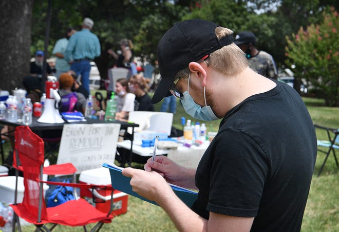 Guy Justusson signs the petition calling for the removal of a Confederate monument on the East lawn of Memorial Auditiorium Monday afternoon. The petition was organized by a BLM Wichita Falls group.