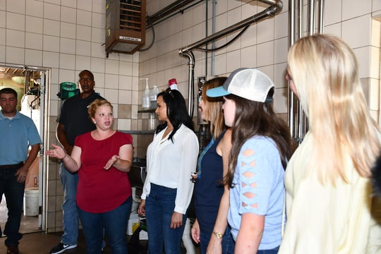 Kelly Oudenhoven, left in red, gives a tour of Larrand Dairy to members of the Trump campaign.