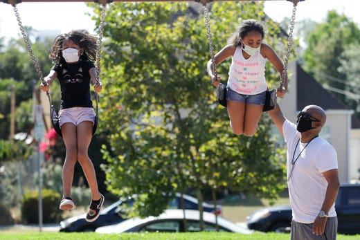 Afework Meshesha, right, pushes his daughter Yohanna while she rides a swing at a playground, Saturday, July 11, 2020, in Los Angeles. The number of deaths per day from the coronavirus in the U.S. had been falling for months, and even remained down as some states saw explosions in cases. But now a long-expected upturn has begun, driven by fatalities in states in the South and West.