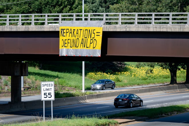 A protest sign hangs above I-240 from the Town Mountain Road bridge on July 14, 2020.