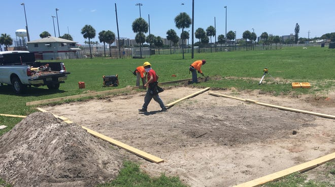 Workers begin construction on the pad area for the discus event at Satellite High School, where the Amateur Athletic Union Junior Olympic Games track and field events will take place.