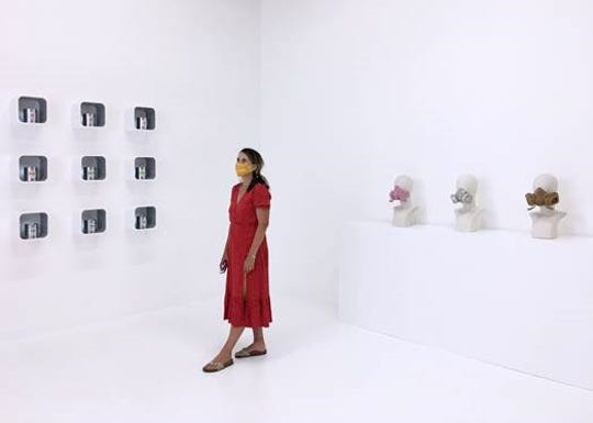 """Artist Dorota Coy stands among her and Steve Coy's work from the exhibition """"The Five Realms"""" currently in display at the Wasserman Project Gallery."""