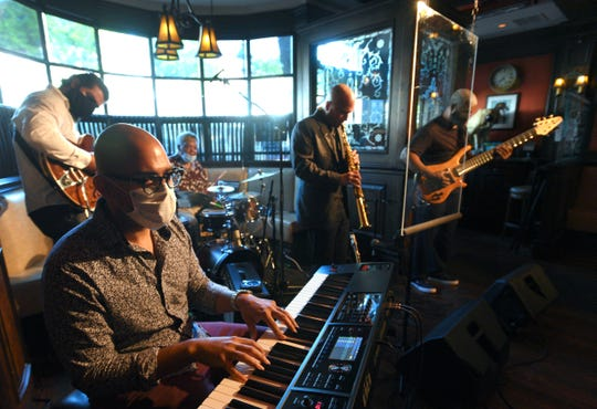 Playing (from left) guitarist Matt Callaway of Monroe, keyboardist Derrick Benford of Detroit, drummer and band founder Gene Dunlap of Southfield, saxophonist Nick Stone of Dearborn and bassist Carl Holmes of Detroit perform behind clear plexiglass screens to a mostly empty Dirty Dog Jazz Cafe in Grosse Pointe Farms on Thursday, July 9, 2020.