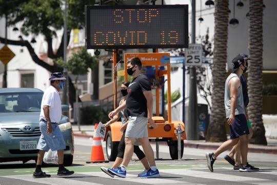 Pedestrians wear masks as they cross a street amid the coronavirus pandemic Sunday, July 12, 2020, in Santa Monica, Calif.