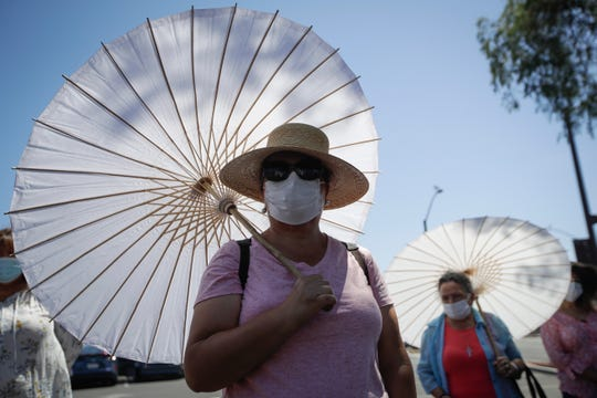 The faithful use face masks and parasols during an outdoor prayer amid the coronavirus pandemic at the San Gabriel Mission, Sunday, July 12, 2020, in San Gabriel, Calif.