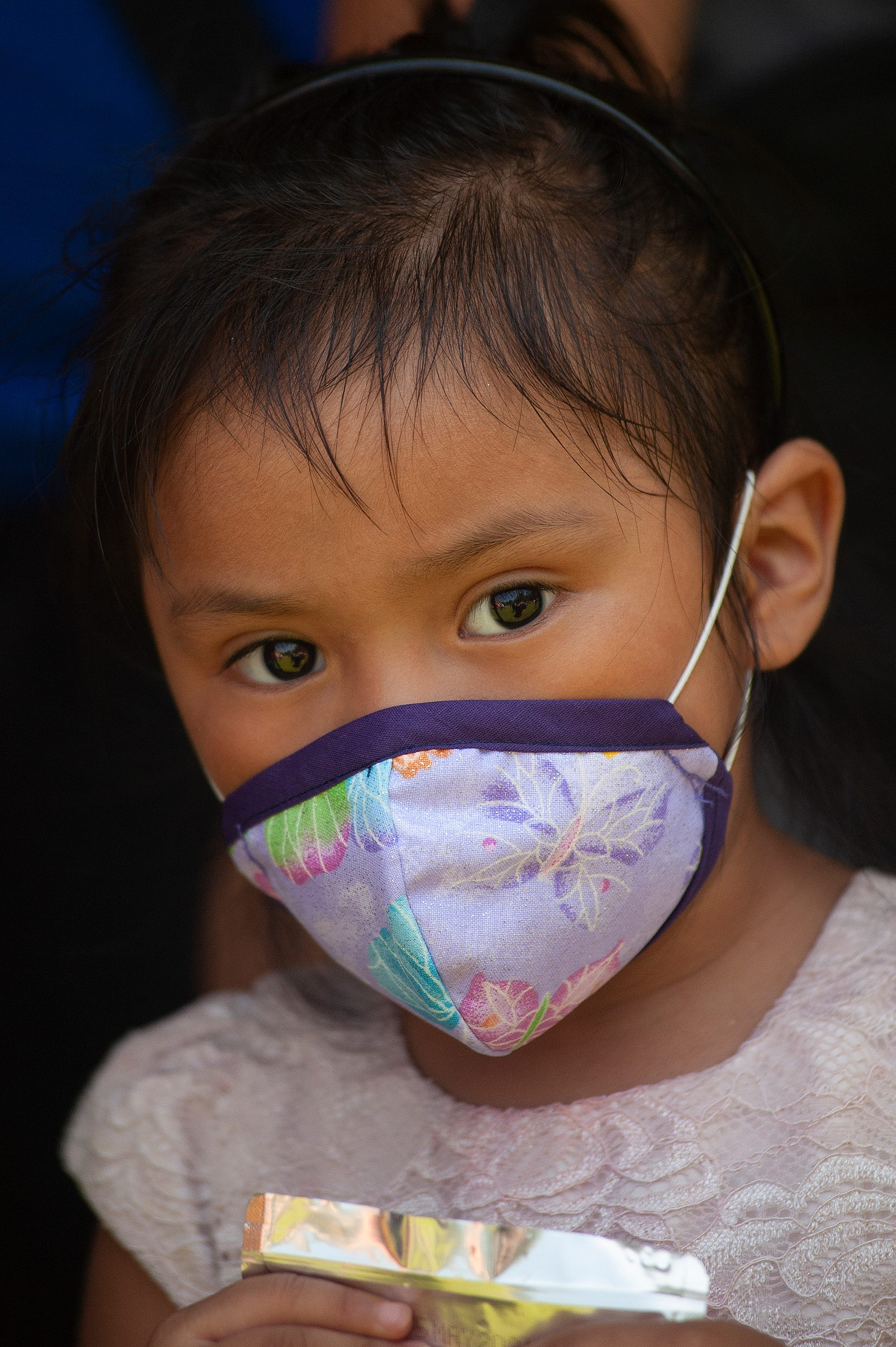Estrella Gabriel Domingo, 3, of Forest, Miss., wears a face mask while at a school supply distribution event hosted by nonprofit El Pueblo to help immigrant families struggling to provide for their families in the aftermath of ICE raids in August 2019 and amid the coronavirus pandemic.