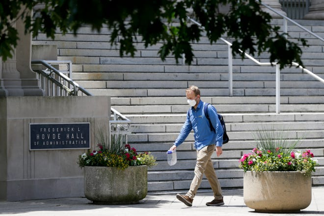 A man walks past Purdue University's Frederick L. Hovde Hall of Administration, Tuesday, July 14, 2020 in West Lafayette.