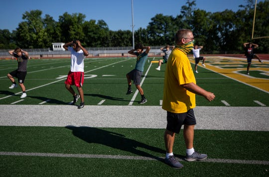 Older coaches are taking precautions to avoid getting the coronavirus while still preparing their teams for the start of the school year and competition. St. Xavier football coach Kevin Wallace keeps an eye on players while maintaining a safe distance. July 14, 2020