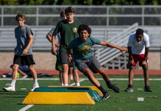 Older coaches are taking precautions to avoid getting the coronavirus while still preparing their teams for the start of the school year and competition. St. Xavier players run through agility drills during a morning practice. July 14, 2020