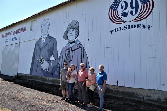 A mural of President Warren G. Harding and First Lady Florence Harding was unveiled Saturday, July 11, 2020, on the side of a barn at Two Sparks Farm, located along Ohio 95 in Claridon Township. Commissioned by the Ohio History Connection, the mural commemorates the 100th anniversary of Harding's election as the 29th President of the United States. Pictured from left to right are the barn's owners Jason and Emma Nutbrown, Marion County Commissioner Kerr Murray and his wife Sharon, and Marion Area Convention & Visitors Bureau Executive Director Mark Holbrook.