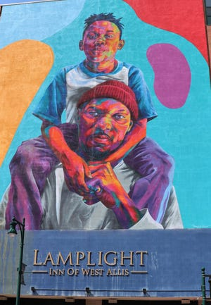 "A new mural showing a son on a father's shoulders graces the wall of the Lamplight Inn at 7400 W. Greenfield Ave. in West Allis. The mural was painted by artist Thomas ""Detour"" Evans of Denver and is part of a city project to add murals to four buildings along Greenfield Avenue."