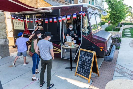 Le Reve Patisserie & Cafe serves customers from the restaurant's food truck at Root Common Park in Wauwatosa on Monday, July 13.