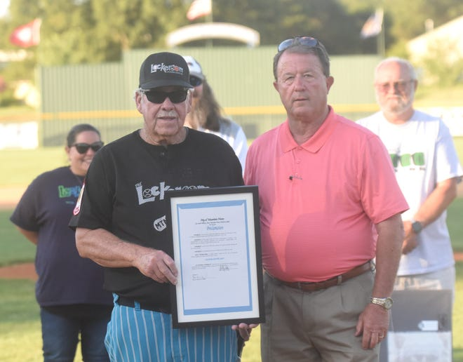 Lockeroom head coach Lester White (left) is presented with a proclamation from the city of Mountain Home by mayor Hillrey Adams on Monday night at Cooper Park.