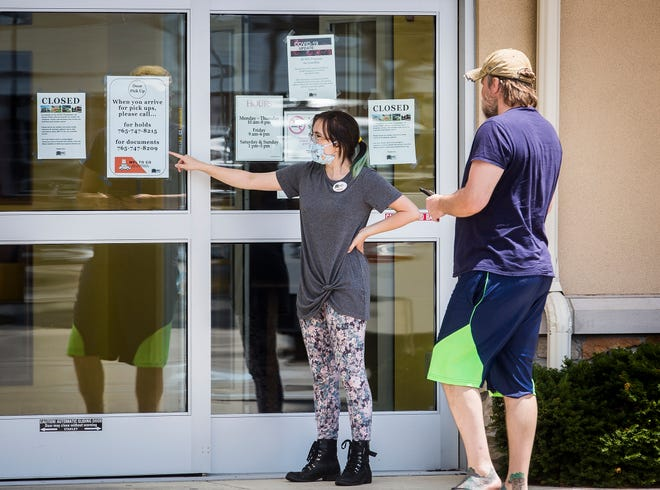 A librarian chats with a member outside of Kennedy Library in July, while the Muncie libraries were closed to visitors but offered curbside service in the parking lots. Library buildings will reopen to the public starting Sept. 8.