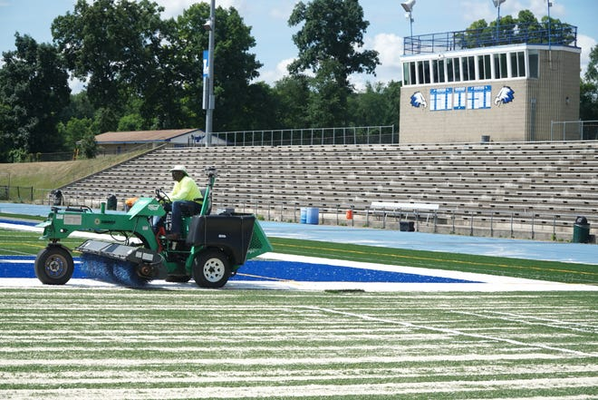 Crews work on spreading a cushioning layer of fine sand on Lakeland High's new artificial turf field at their stadium on July 14, 2020.
