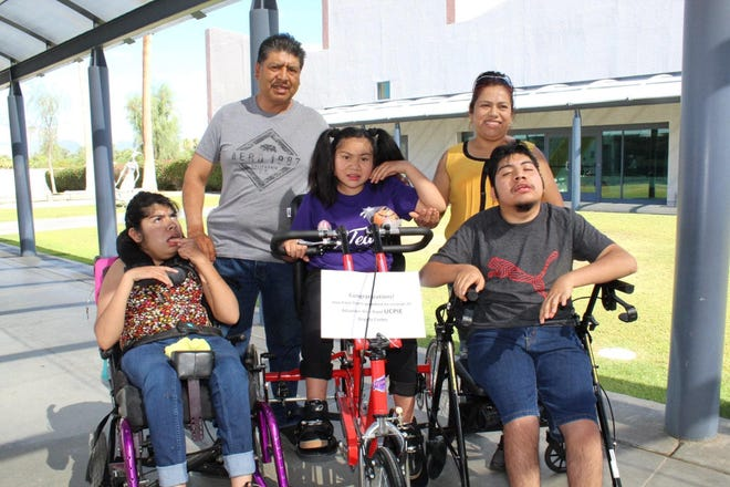 Santos and Bellita Cortes with their three children, Yaneira, Ángela and Heriberto, who were gifted with adaptive bikes from UCPIE.