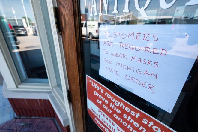 A sign telling customers that masks are required hangs on the door of Everything Classics Antiques Tuesday, July 14, 2020, in downtown Port Huron. Starting Monday, under a new executive order, Michiganders are required to wear face coverings in public indoor and crowded outdoor spaces,