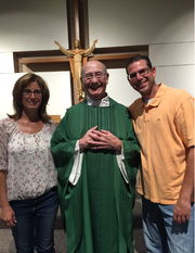 Mark and Donna Roerick smile for a photograph with Rev. Nick Landsberger (center).