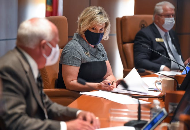 Indian River County Commission Chairman Susan Adams (center), glances back at Peter O'Bryan (left)  as they discuss the proposed mandatory mask mandate during their county commission meeting on Tuesday, July 14, 2020, in Vero Beach.