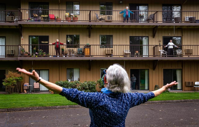 Fitness coordinator Janet Hollander leads session of Balcony Boogie from outside Willamette Oaks in Eugene, Ore. for residents isolated in apartments during pandemic, April 21, 2020.