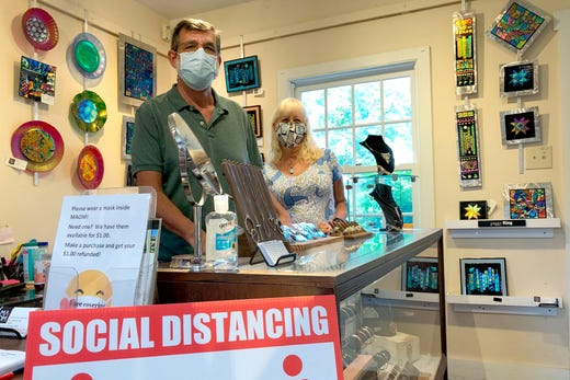 Artists Jack Schwab, and Debbie Wilger, wear their masks July 14, 2020, inside the Missouri Artists on Main store in downtown St. Charles, Mo. Schwab, 60, who makes silver jewelry, and Wilger, 63, a painter, are concerned about the uptick in coronavirus cases in St. Charles County, and say most customers in the store abide by their facial covering policy, but a few have left in anger because of it.