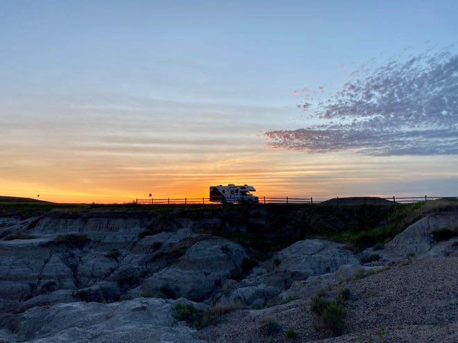 The RV is parked as the sun rises at Badlands National Park.