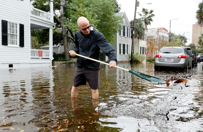 Rob Kramer removes debris from a drain as tidal flooding inundated many downtown streets in Charleston on Oct. 27, 2015. Just weeks after historic rains drenched the state, more flooding along the South Carolina coast brought another round of astronomical high tides often called king tides.