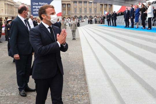 TOPSHOT - French President Emmanuel Macron greets visitors after Paris' traditional Bastille Day parade, which was scaled back this year due to COVID-19.
