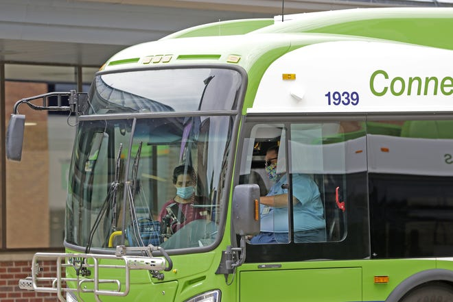 A bus driver and passenger wear masks on a bus at the Appleton Transit Center on Tuesday in Appleton.